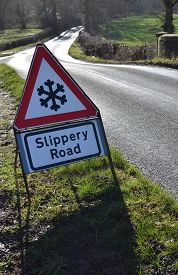 stock photo of slippery-roads  - Warning road traffic sign informing that there is ice on the road causing the road surface to be slippery - JPG