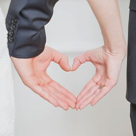 stock photo of hand heart  - wedding couple showing shape of heart from their hands - JPG