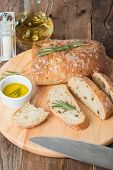 picture of fresh slice bread  - Sliced bread Ciabatta and rosemary on wooden background - JPG