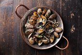 picture of clam  - Shells vongole venus clams in copper cooking dish on dark wooden background - JPG