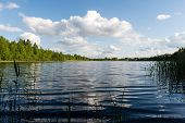 image of bent over  - White clouds on the blue sky over blue lake with reflections - JPG