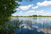 stock photo of bent over  - White clouds on the blue sky over blue lake with reflections - JPG