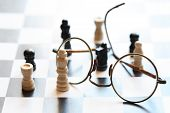 stock photo of spectacles  - Black and white chessman set near spectacles on chessboard against light - JPG
