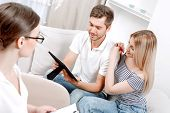 picture of psychologist  - Young couple sitting on a couch at the doctors office and looking at a photo in a frame smiling - JPG
