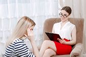 image of woman red blouse  - Beautiful psychologist sitting in an armchair wearing white blouse red skirt and glasses listening to her patient woman telling about her problems holding her head - JPG