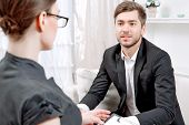 stock photo of psychologist  - Young man wearing a black suit sitting on a couch looking at his doctor and listening - JPG
