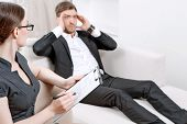 foto of psychologist  - Young man wearing a black suit lying on a couch telling his problems and holding hands near head - JPG