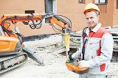 stock photo of millwright  - builder worker in safety protective equipment operating construction demolition machine robot - JPG
