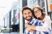 picture of piggyback ride  - Portrait of happy man giving piggyback ride to woman in city - JPG