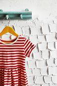 foto of habilis  - Child dress on hanger on white wall background - JPG