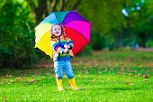 picture of rain  - Child with colorful umbrella playing in the rain - JPG