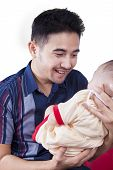 foto of happy baby boy  - Happy young father holds a three months baby boy and smiling at the baby isolated on white - JPG