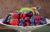 foto of fruit bowl  - Summer Fruit including raspberries strawberries cherries blueberries and kiwi fruit in a vintage bowl with reclaimed dark wood background - JPG