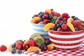 image of fruit bowl  - Fresh colorful fruit including raspberries strawberries cherries blueberries manadrines and kiwi fruit in breakfast bowls on red check placemat on shabby chic white wood table - JPG
