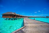 stock photo of jetties  - Water bungalows and wooden jetty with turquiose water on Maldives - JPG
