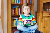 foto of daycare  - Active kid boy holding photocamera in hands indoors - JPG