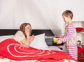 stock photo of bed breakfast  - Little son giving a tray with breakfast to his mom laying in bed - JPG