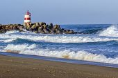stock photo of inlet  - Ocean view and small lighthouse in the inlet jetty of Tavira Island Algarve Portugal - JPG