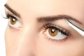 stock photo of eyebrows  - Young woman plucking eyebrows with tweezers close up - JPG