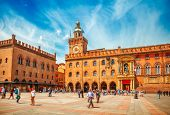 Italy Piazza Maggiore in Bologna old town tower of hall with big clock and blue sky on background. A poster
