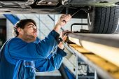 Young male mechanic changing tire from suspended car at automobile shop poster