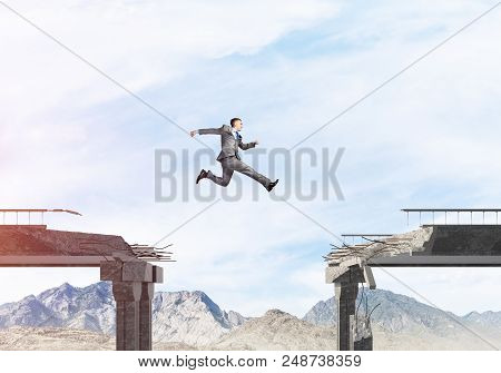 poster of Businessman Jumping Over Huge Gap In Concrete Bridge As Symbol Of Overcoming Challenges. Skyscape An
