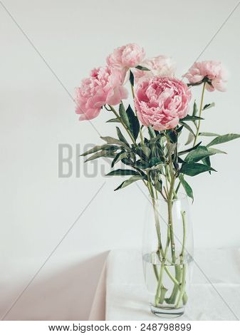 Beautiful Pale Pink Peony Bouquet In Glass Vase On Table With White
