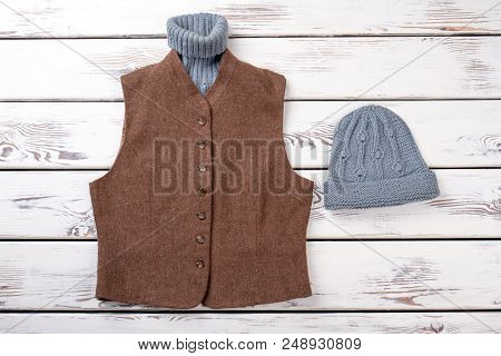 poster of Woolen Sweater In Brown Jacket And Hat. Grey And Brown Winter Clothing. White Wooden Background, Fla