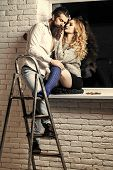Love Relationship. Couple In Love Hug On Window Sill. Woman With Long Hair And Man Hipster On Stepla poster