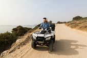 Young Woman Driving Rental Quad Bike On Seaside Road In Naxos Island, Greece poster