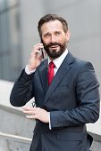 Business Man Talking Active With The Client On A Cell Phone Out Of Office Building. Handsome Bearded poster