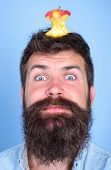 Hipster Happy Face With Apple Stump Target On Head Blue Background, Close Up. Man Handsome Hipster L poster