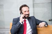 On The Phone. Portrait Of Modern Businessman Talking On Smart-phone While Sitting On Bench Outdoors. poster