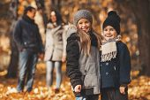 Young Family Of Four Have Fun In Autumn Park. Happy Time Spending Outdoor Concept. Young Family Havi poster