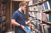 Man Stands In A Public Library With Books In His Hands. A Student Is Looking For Books In An Old Pub poster
