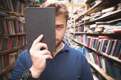 Portrait Of A Student Standing In The Library, Covering The Face With A Black Book And Looking Into  poster
