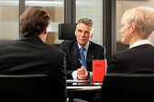 stock photo of lawyer  - Mature lawyer or notary with clients in his office in a meeting - JPG