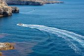 A Motor Boat Speeds Across A Blue Ocean poster