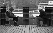 Couple Sitting Together On A Jetty, Gazing At  River View poster