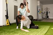 Physical Therapist Assisting Young Caucasian Woman With Exercise With Dumbbell During Rehabilitation poster