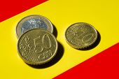 stock photo of spanish money  - A few Euro coins on top of the Spanish flag - JPG