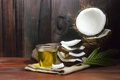 Coconut Oil With Coconut Half And Coconut Pieces And Leaf  On Wooden Table And Black Wooden Backgrou poster