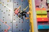 kid, child having fun on a climbing wall in an indoor climbing center, active healthy lifestyle, act poster