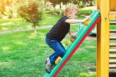 Happy Kid Climbing On Outdoor Playground. Little Blond Boy Having Fun Outdoors. Summer, Spring And A poster