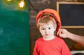 Toddler In Protective Hard Hat, Helmet At Home In Workshop. Carefully Protect Kid With Helmet. Prote poster