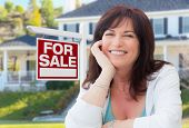 Middle Aged Woman In Front of House with For Sale Real Estate Sign In Yard. poster