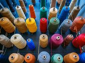Colorful Background. Many Colorful Coils And Spools Of Colored Wool Thread Stand On The Holders. poster