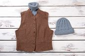 Woolen Sweater In Brown Jacket And Hat. Grey And Brown Winter Clothing. White Wooden Background, Fla poster