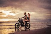 Affectionate Couple Sitting On Motorcycle At Beach During Sunrise poster