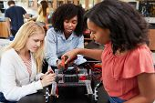 Teacher With Female Pupils Building Robotic Vehicle In Science Lesson poster
